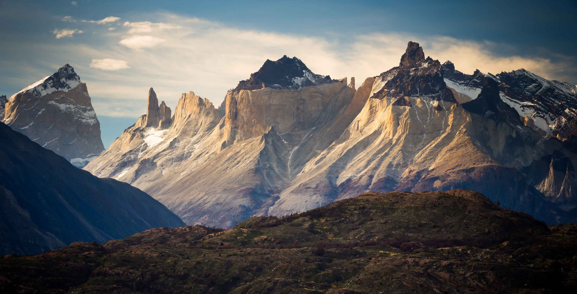 The spires of Torres del Paine National Park in Patagonia, Chile look down on Lago Grey, a glacially fed lake on the west side of the park. Grey Glacier, which is nearly four miles wide and 90 feet thick, often calves large icebergs that float into the lake.