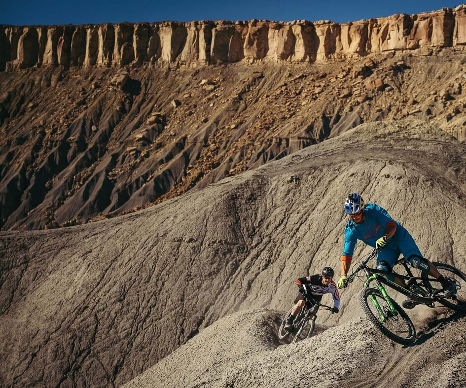 Desert ridges trickle down from the Cainveille Mesas, offering endless spine lines all the way to the valley floor—or from the valley floor back up, depending on your bike of choice. Darren and Ricky go gravity powered down the spines.