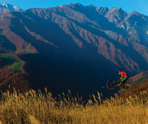 The mountains surrounding the Hakuba Valley are known as the Japanese Alps for good reason. With 10,000-foot-tall peaks, endless valleys and a handful of ski resorts, one of which is developing a bike park, there's no shortage of opportunity for trails. The author soars through the landscape on a newly minted jump line at Hakuba Iwatake Mountain Resort.