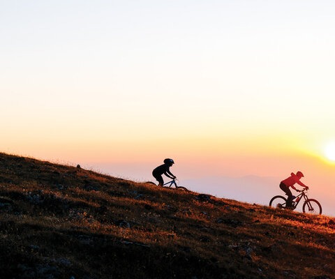 Nicki Trimble and Erin Bergey ride through the last flush of color on a dusk-lit descent in the Big Belt Mountains of Montana. Classified as an island range, the Big Belts are isolated as if adrift in a sea of Montana's vast prairies and flatlands.