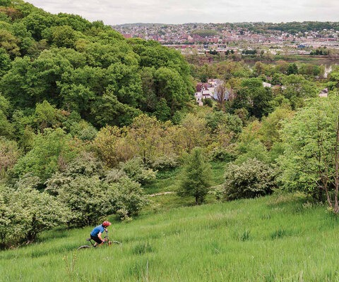 Anna Barensfeld takes in the view of Homestead, a town located just across the Monongahela River from Pittsburgh, as she rides High Traverse at the southern end of Frick Park's trail system. Stacks from old mills remain as historical landmarks in the area though the factories of Henry Clay Frick's empire are long gone.