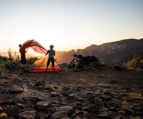 As soon as the sun sets in Arizona's high desert, the temperature drops quick. Stan Jorgensen and Jackie Paaso get a jump on setting up camp while the light still lingers.