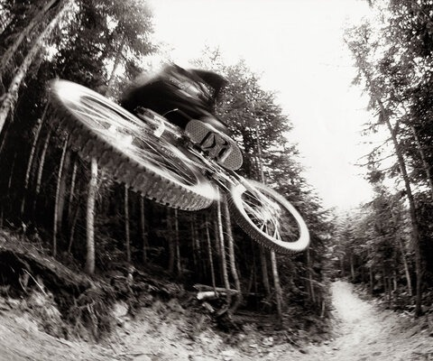 Even before it was finished, builders and riders alike knew A-Line was something special. Richie Schley gets a little taste of the now-famous trail before anyone else, while the trail crew's Marty Gautrey uses an excavator to build even more jumps around the corner.  Photo: Blake Jorgenson
