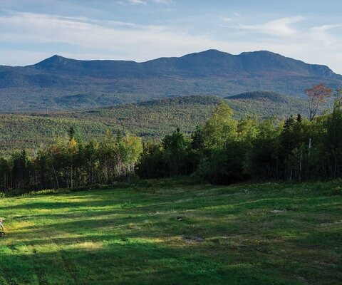 Peter Cole drops into the West Knoll trail just after sunrise, with Bigelow Mountain serving as an impressive backdrop over the north side of Carrabassett Valley. 57